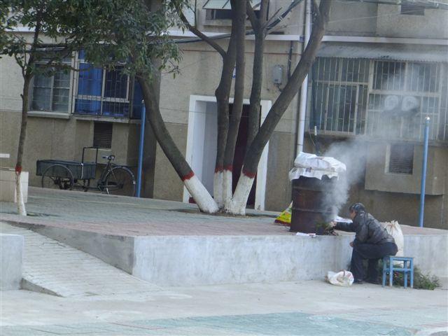 南阳网讯 (见习记者单衣上路)临近年底,市区居民都在准备年货,1月5日,记者发现,在市区小区内有人在自家门口熏制过年用的腊肉,如此做法污染了自己门口的空气,实在是得不偿失。      1月5日上午10点,记者从油田双河新苑小区路过,在小区32号楼附近,发现有浓烟冒起。记者在楼房附近发现,有人在用自制的熏炉熏制腊肉。记者看到,有几个居民蹲在油桶改造成的熏炉跟前,不停地往熏炉里填烧松枝柏桠。熏炉的上方,放着一条条猪肉,猪肉用报纸遮盖着,靠下面起的烟气熏烤。熏炉冒出来的烟气,不断地飘向空中,污染着洁净的空气