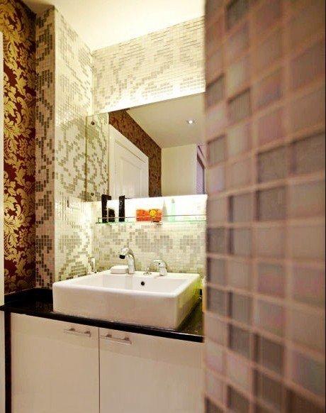 长条形的浴室镜后嵌着照明灯,设计独特,方形洗手池下是白色 储物柜