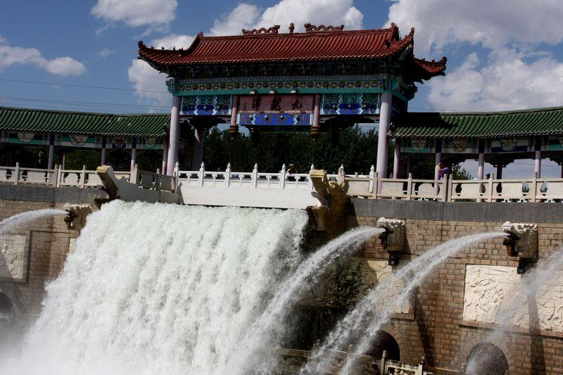 秋薇子 发表于 2012-10-16 16:17  九龙潭是克拉玛依河的源头所在,地处克拉玛依河穿城风景带之首东郊瀑布景区内。该景区主要由高约8米的人工瀑布、瀑布下的巨潭和周围大面积的绿化林带草坪构成。 瀑布水源来自风克干渠湍急的水流从中间的一条巨龙口中喷出,利用水的喷涌速度和自然重力形成宽约10米的巨大的瀑布,瀑布的两边分列的8条龙嘴也同时喷出水柱,构成一副巨大的水廊。瀑布下面是一个巨大的长方形回字水潭,潭内碧波荡漾,潭上东西两侧各有一座小拱桥连接潭中的岛屿,成为横跨巨潭的通途。巨潭四周是花岗岩铺面的平