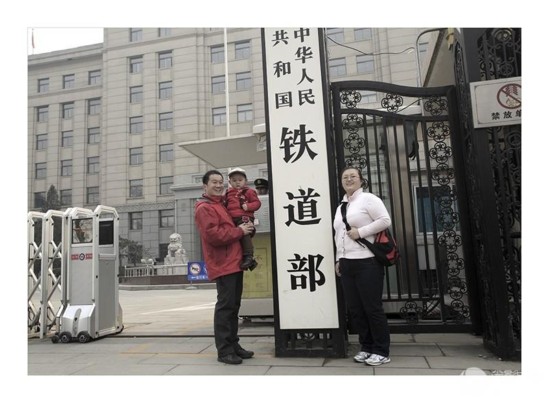 《铁道部换牌情未了》-2  2013年3月15日,北京,在原铁道部门前,一家三口人合影留念。.jpg