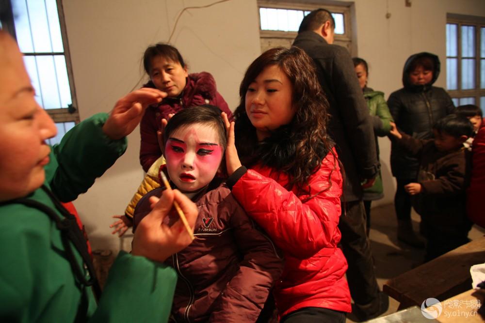 艰苦的传承-3q    2012年1月31日,河南省浚县正月古庙会上,一名儿童在化妆.jpg