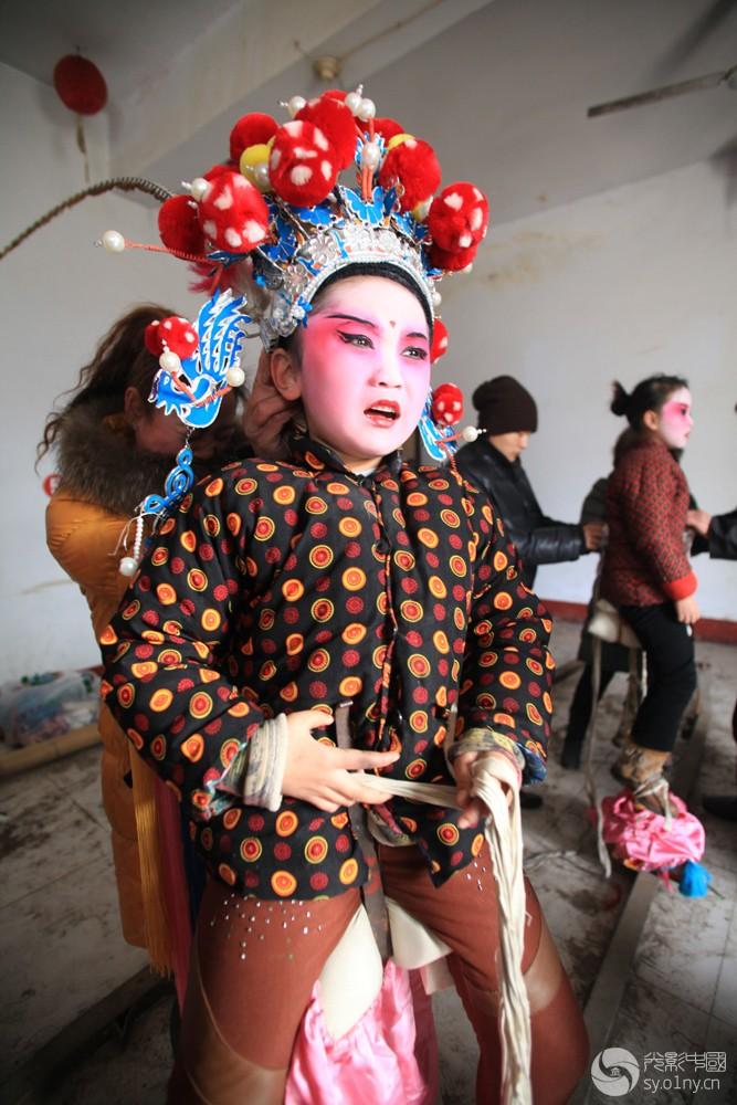 艰苦的传承-4   2012年1月31日,河南省浚县正月古庙会上,一名儿童在做准备。.jpg