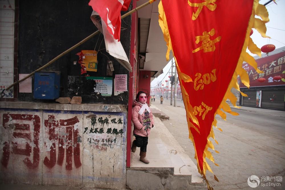 艰苦的传承-6   q2012年1月31日,河南省浚县正月古庙会上,一名儿童在化妆中逃出来不.jpg