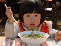马街书会上吃烩面的小女孩