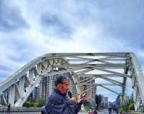 《老大爷网红桥上自娱自乐》(手机拍摄)